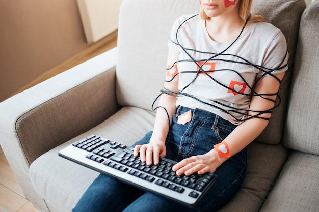 La giovane donna ha una dipendenza dai social media. taglia vista. digitando sulla tastiera. corpo avvolto con cordoncino. dipendenza da laptop o smartphone. ostaggio sui social media.