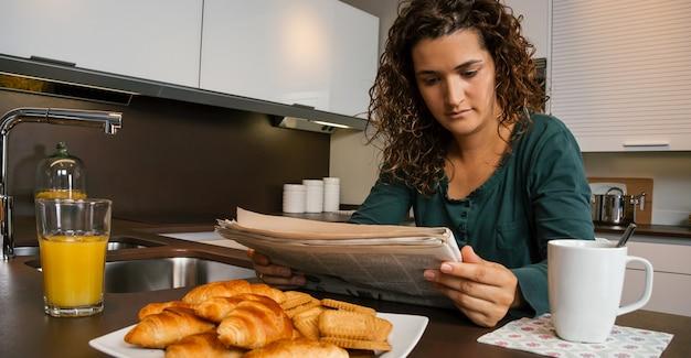 Giovane donna che fa colazione in cucina e guarda il giornale