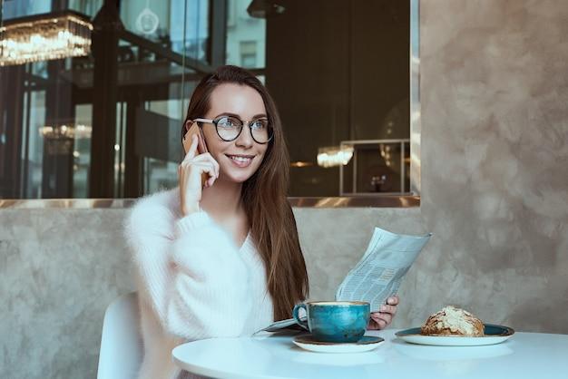 Giovane donna che mangia una colazione con il giornale della lettura del croissant e del caffè all'aperto al terrazzo francese tipico del caffè in francia