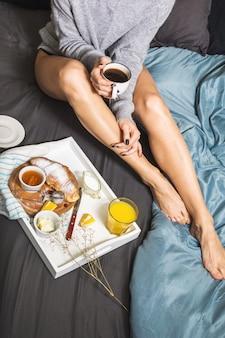 Giovane donna che fa colazione con caffè, croissant e succo d'arancia a letto