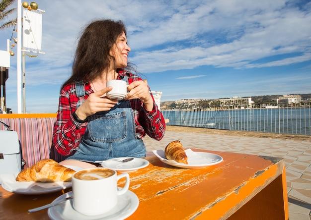 Giovane donna che fa colazione con croissant e caffè al bar sulla strada di fronte al mare.