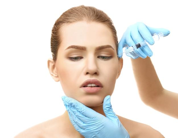 Giovane donna che ha iniezione cosmetica su bianco. concetto di chirurgia plastica