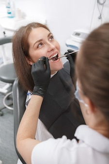 Giovane donna che ha un trattamento dentale dal dentista professionista