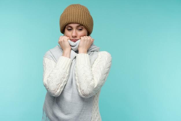 Giovane donna con canna fumaria su sfondo blu. la bella signora è malata di febbre alta e mal di gola