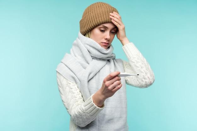 Giovane donna con canna fumaria tenendo termometro su sfondo blu. la bella signora è malata di febbre alta e mal di testa, primo piano isolato. freddo, concetto di influenza.
