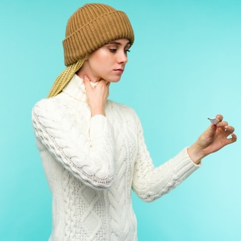 Giovane donna con canna fumaria tenendo termometro su sfondo blu. la bella signora è malata di febbre alta e mal di gola, primo piano isolato. freddo, concetto di influenza.