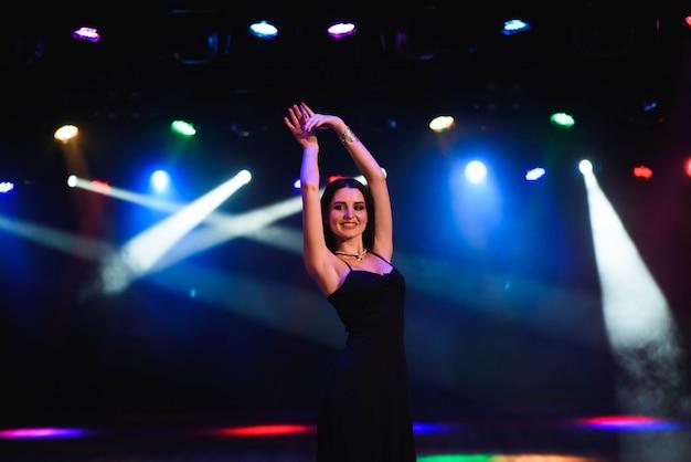 Giovane donna che si diverte, impazzendo da solo, trucco sexy luminoso, festa divertente, immagine notturna con flash.
