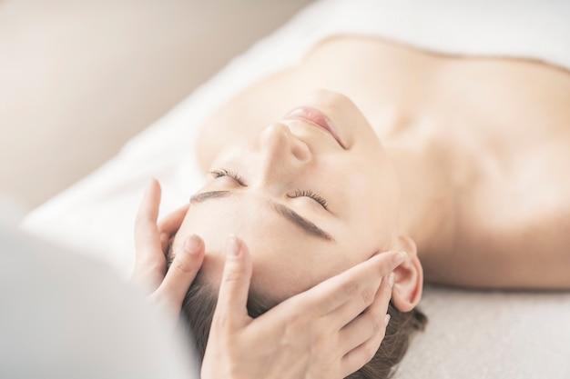 Giovane donna con la testa massaggiata presso il salone di bellezza