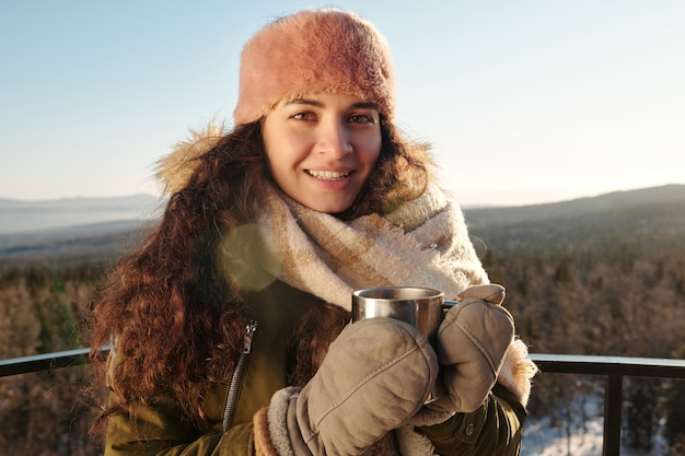 Giovane donna che mangia tè caldo contro il bellissimo paesaggio in inverno day