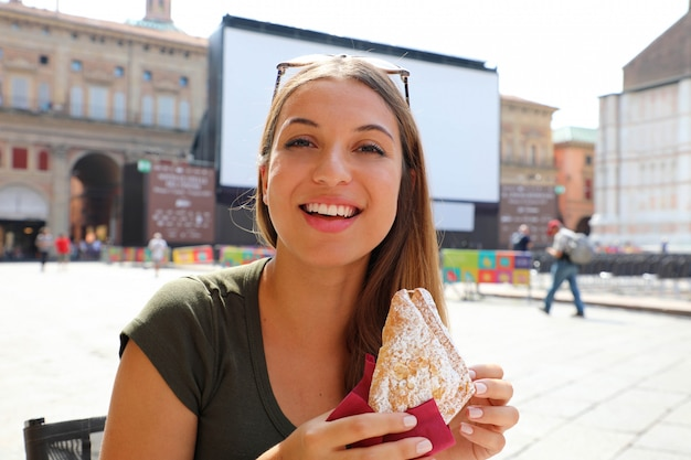 Giovane donna con colazione italiana con croissant e caffè al bar sulla strada in estate in italia