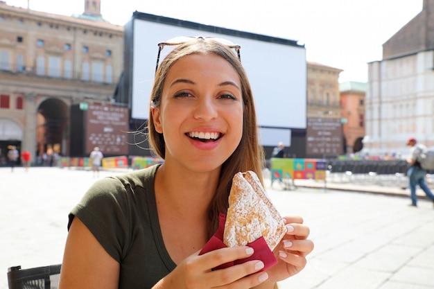 Giovane donna con colazione italiana con croissant e caffè presso il bar sulla strada in estate