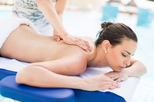 Giovane donna con massaggio in piscina