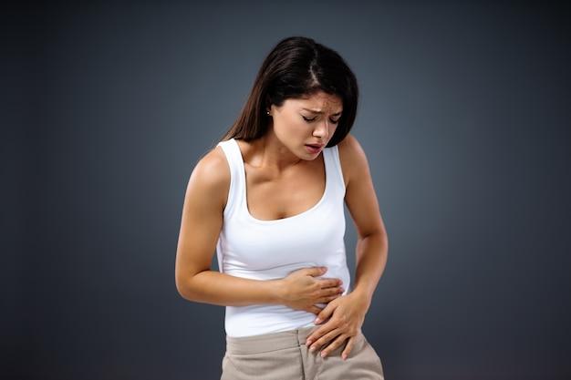 Giovane donna che ha dolore allo stomaco così forte che si piega e tiene lo stomaco.