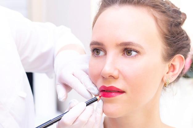 Giovane donna con trucco permanente sulle labbra al salone di estetiste