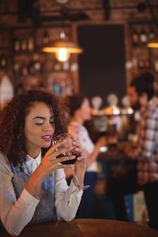 Giovane donna con vino rosso nel pub