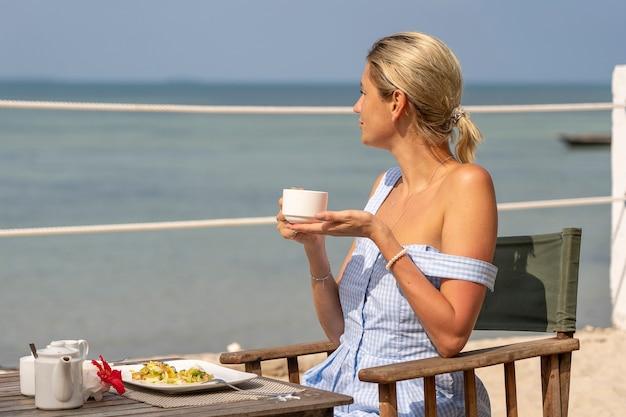 Giovane donna che fa colazione romantica nel ristorante dell'hotel durante l'alba vicino all'acqua di mare sulla spiaggia tropicale, primo piano. la ragazza si sta godendo l'alba con una tazza di caffè bianca e del cibo sul tavolo