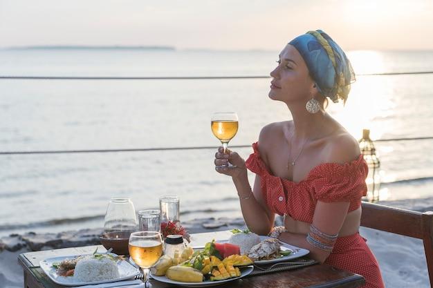 Giovane donna che ha una cena romantica nel ristorante dell'hotel durante il tramonto vicino alle onde del mare sulla spiaggia tropicale, primo piano. la ragazza si sta godendo il tramonto con un bicchiere di vino. concetto di svago e viaggio