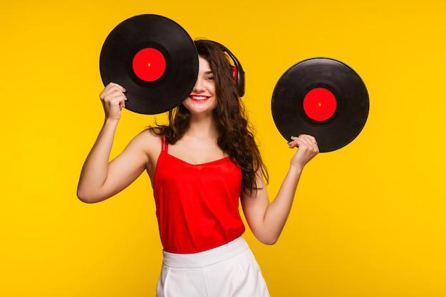 Giovane donna in cuffie che guarda l'obbiettivo e chiudendo il viso con il disco in vinile. - immagine