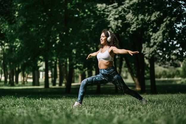 Giovane donna in cuffie che esegue esercizi di fitness nel pa