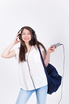 Giovane donna in cuffie a cantare canzoni su un muro bianco