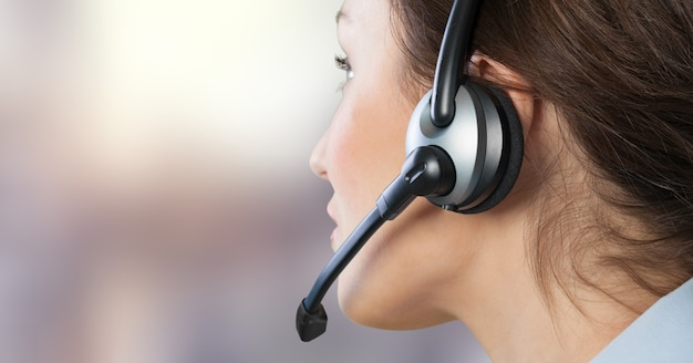 Una giovane donna in cuffia con microfono che lavora in un call center