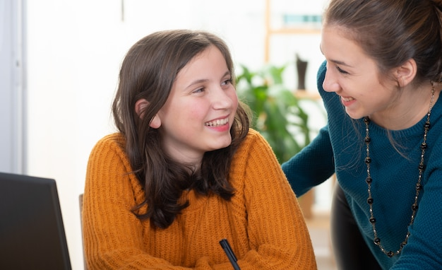 La giovane donna aiuta una ragazza teenager con i compiti