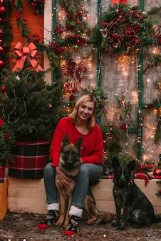 Giovane donna e i suoi cani in decorazioni natalizie