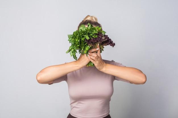 Giovane donna che nasconde il viso dietro un mazzo di erbe, verdure a foglia verde, con in mano lattuga acetosella e sorridente guardando la fotocamera, alimentazione sana, cibo biologico. foto in studio, sfondo grigio