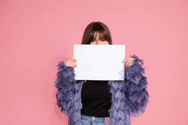 Giovane donna che si nasconde dietro un foglio di carta bianco bianco per un'iscrizione. su sfondo rosa in studio. persona irriconoscibile.