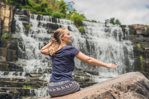 Turista della viandante della giovane donna sullo sfondo dell'incredibile cascata pongour