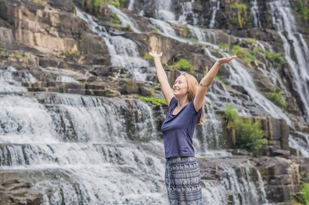 Giovane donna escursionista, turista sulla superficie di amazing pongour waterfall è famosa e la più bella dell'autunno in vietnam