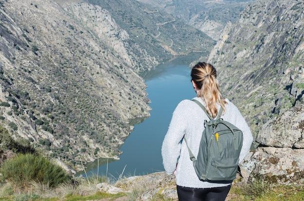 Giovane donna che fa un'escursione in montagna.