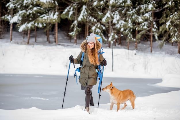 Giovane donna che fa un'escursione con il cane vicino al lago ghiacciato e alla foresta innevata