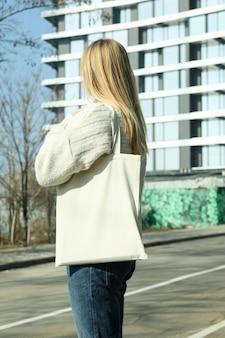 La giovane donna tiene la borsa in bianco di eco all'aperto contro l'edificio a più piani