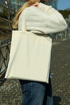 Giovane donna tenere vuoto eco borsa all'aperto