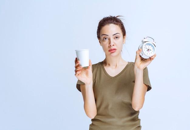 Giovane donna con in mano una sveglia e una tazza di bevanda che indica la routine mattutina
