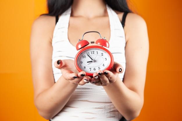 Giovane donna che tiene una sveglia su sfondo arancione