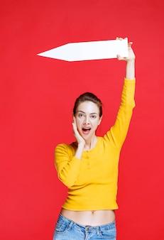 Giovane donna che tiene una freccia che punta a sinistra e sembra sorpresa