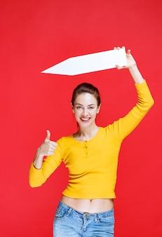 Giovane donna che tiene una freccia che punta a sinistra e mostra un segno positivo con la mano