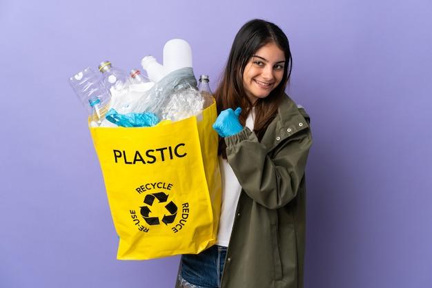 Giovane donna che tiene un sacchetto pieno di bottiglie di plastica da riciclare isolato su viola orgoglioso e soddisfatto di sé
