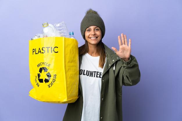 Giovane donna che tiene un sacchetto pieno di plastica che conta cinque con le dita