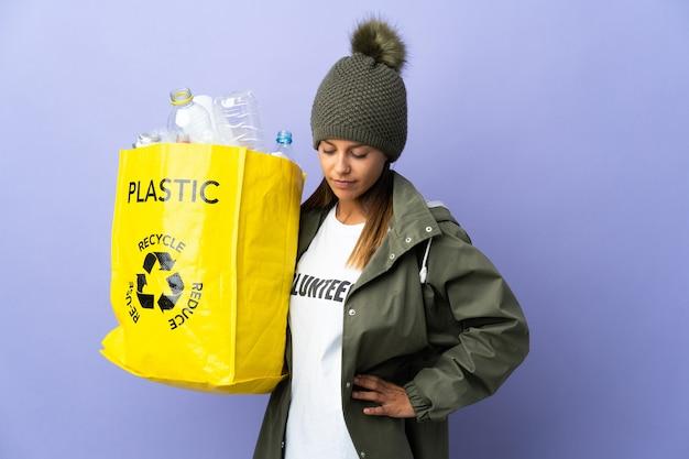 Giovane donna che tiene un sacchetto pieno di plastica che soffre di mal di schiena