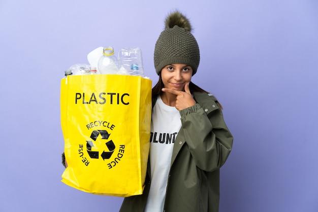 Giovane donna che tiene una borsa piena di pensiero di plastica