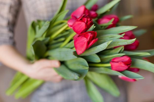 Giovane donna che tiene in mano un bellissimo bouquet primaverile di tulipani rossi