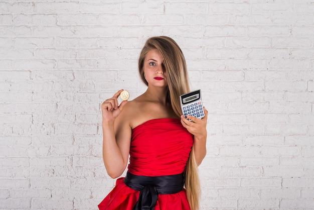 Giovane donna che tiene bitcoin e calcolatrice