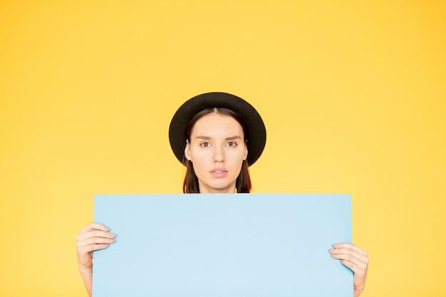 Giovane donna che tiene un manifesto in bianco