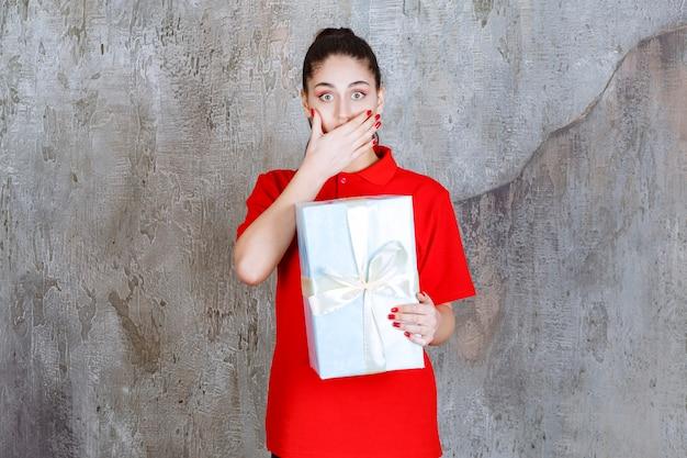 Giovane donna che tiene una confezione regalo blu avvolta con nastro bianco e sembra stressata o terrorizzata.