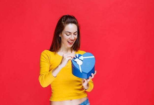 Giovane donna in possesso di una confezione regalo blu a forma di cuore, aprendola e rimanendo sorpresa