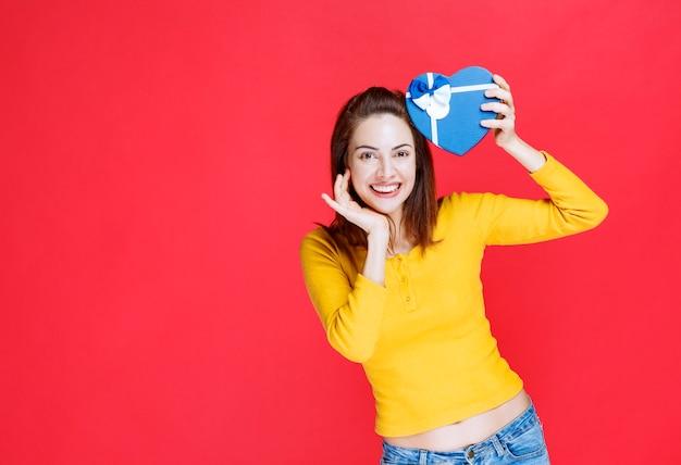 Giovane donna che tiene una confezione regalo a forma di cuore blu