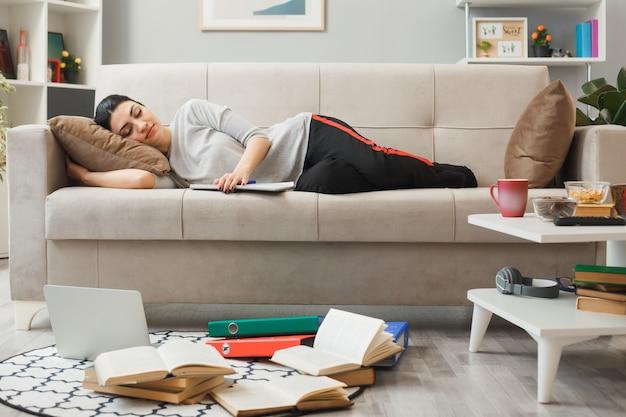 Giovane donna con libro sdraiato sul divano in soggiorno
